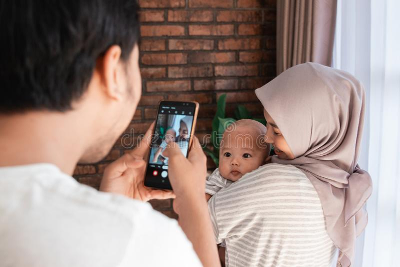 Father taking photo of his baby infant at home while being carried by mother stock photos