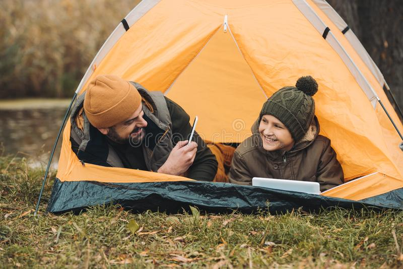 Father taking photo of son. In a tent stock image