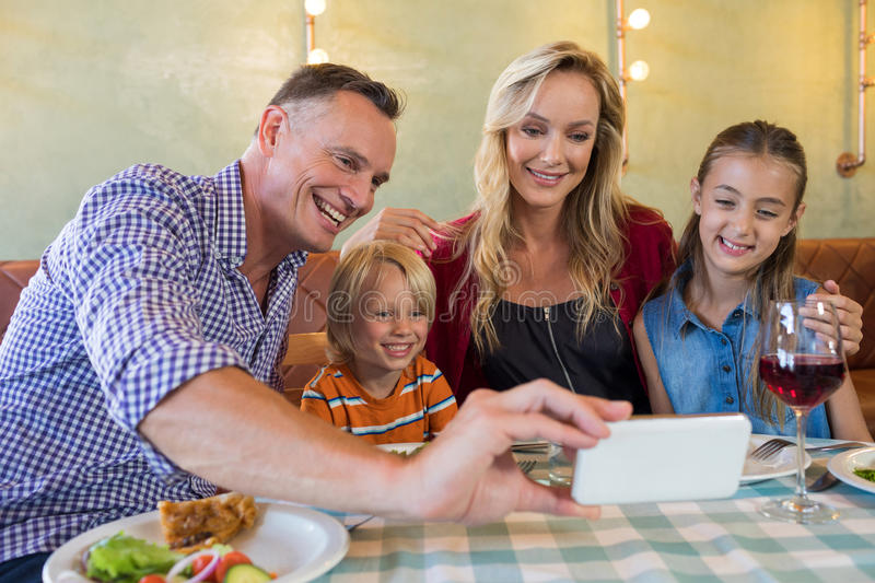 Father taking selfie with family at restaurant. Father taking selfie with family while sitting at restaurant stock image