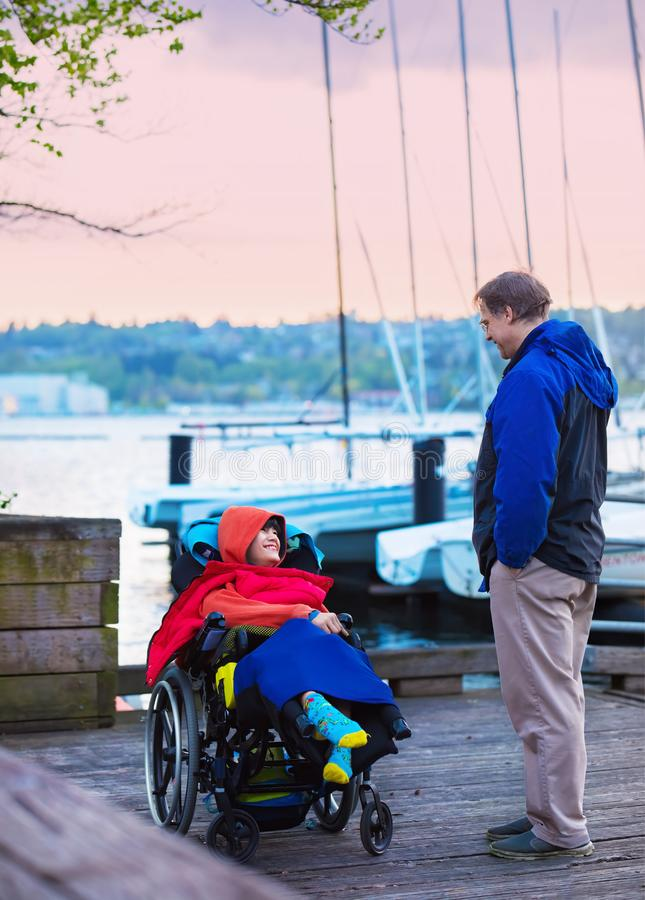 Father talking to disabled son in wheelchair  on wooden pier royalty free stock image