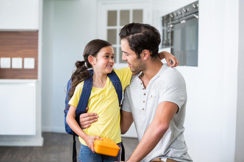 Father talking to smiling daughter holding lunch box. At home stock photos