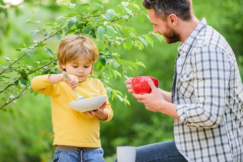 Father teach son eat natural food. Little boy and dad eat. Nutrition kids and adults. Organic nutrition. Healthy royalty free stock photo