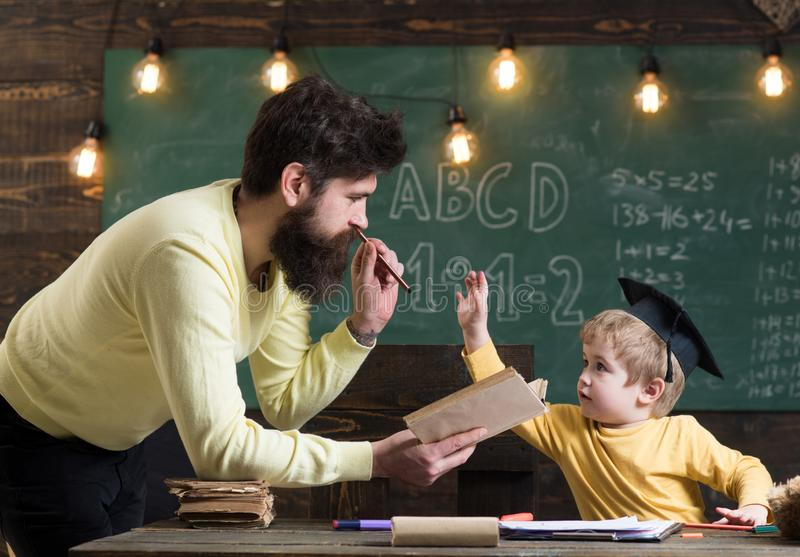 Father, teacher reading book, teaching kid, son, chalkboard on background. Dad wants to grow up genius son. Boy child in. Graduate cap likes to listening dad stock photo