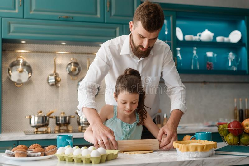 Father teaches daughter to cook stock photo