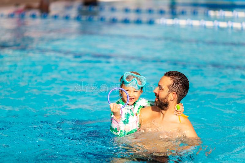 Dad teaches a little daughter to swim in the pool royalty free stock photo