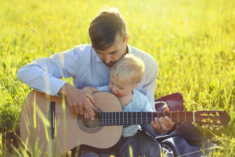 Father teaches his son to play guitar on summer meadow. Time together dad and son outdoor.  royalty free stock photography