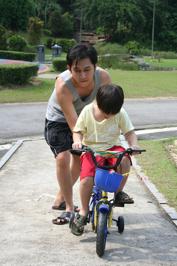 Father teaches son cycling. At the park in the evening royalty free stock image