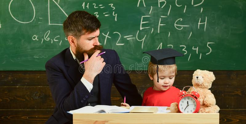Father teaches son, discuss, explain. Kid studying with teacher. Elementary education. Teacher in formal wear and pupil royalty free stock photo