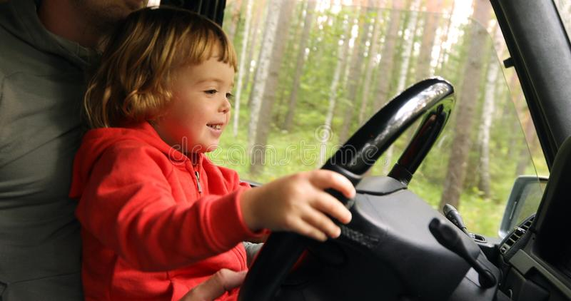 Happy little kid driving car with father royalty free stock photography