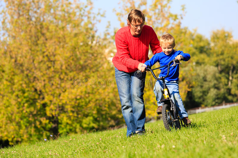 Father teaches son to ride bicycle outdoors stock photos