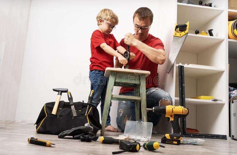 Father teaches son to work with a hand drill. stock image