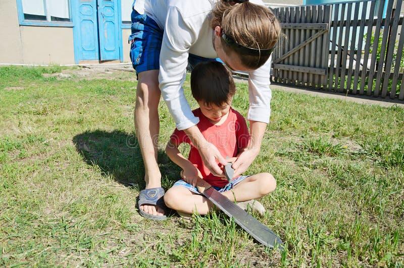 Father teaching boy in machete sharpening royalty free stock photo