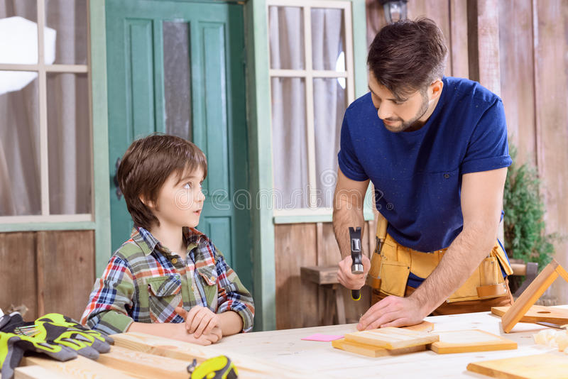 Father teaching concentrated son how to hammering nail in wooden plank stock photography