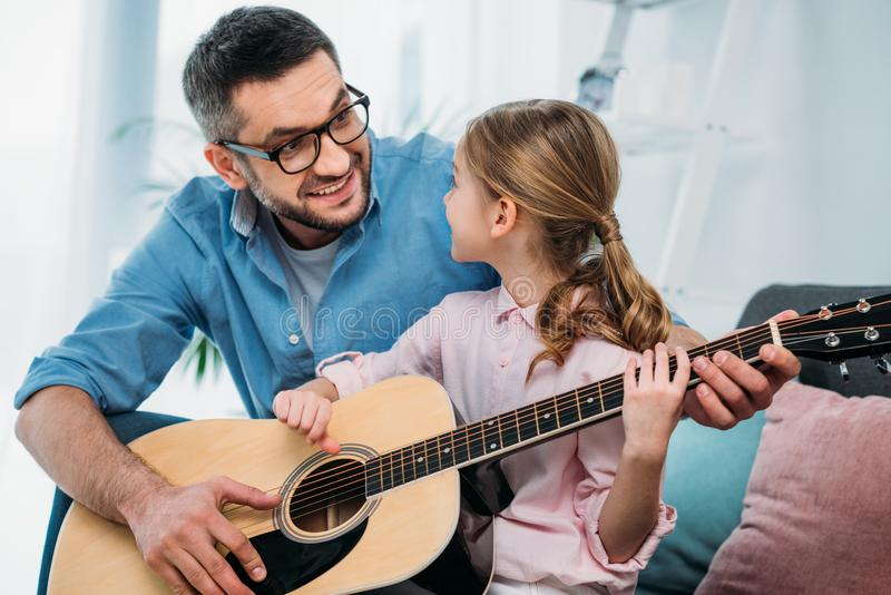 father teaching daughter play guitar royalty free stock image