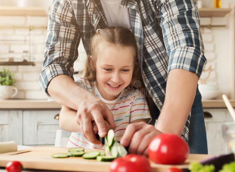 Father teaching daughter to cut a cucumber royalty free stock photo