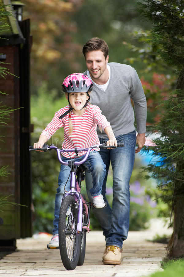 Father Teaching Daughter To Ride Bike In Garden royalty free stock image