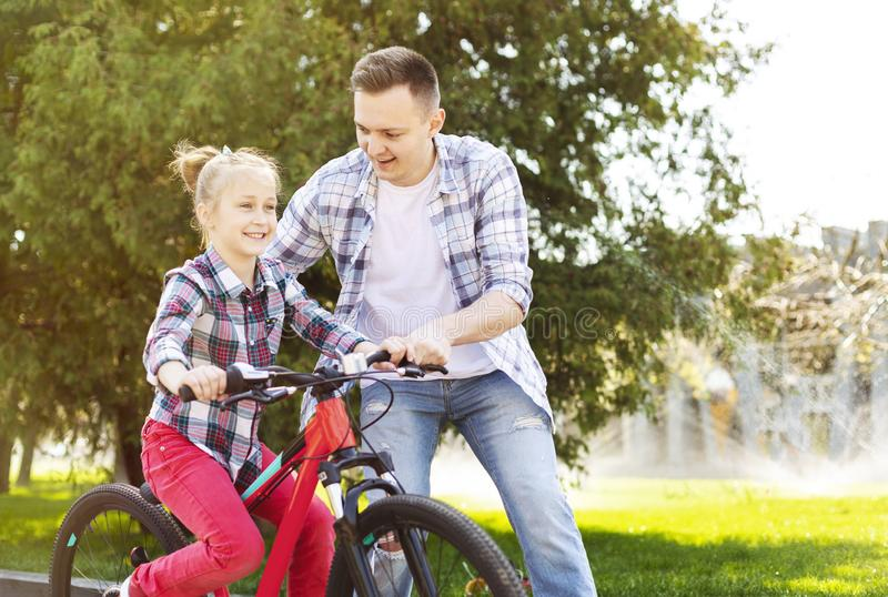 Little girl is learning cycling with her dad stock images