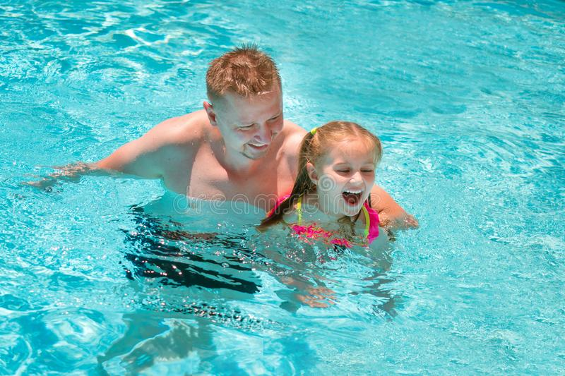 Father teaching his daughter to swim in swimming pool royalty free stock images