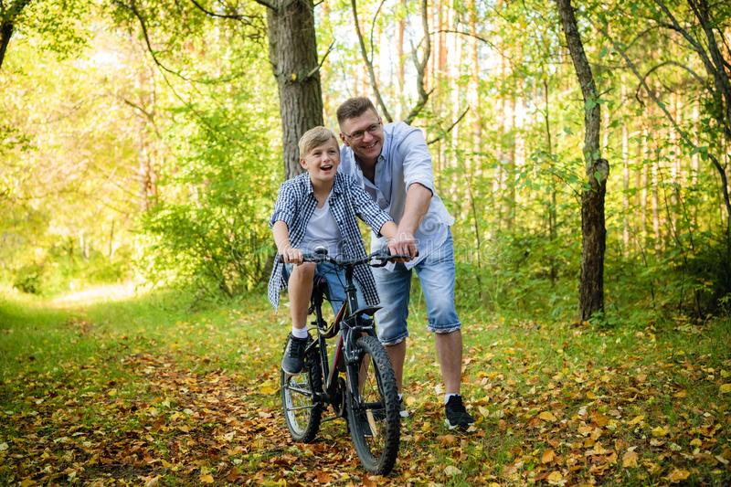 Father teaching his son to ride a bike in a autumn park royalty free stock photos