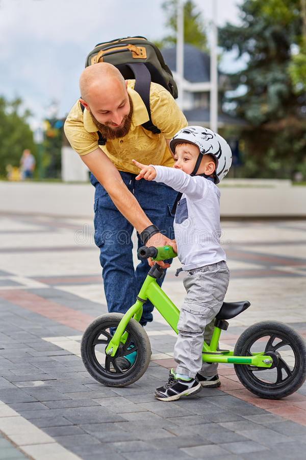 Father teaching his son to ride a bike royalty free stock photography