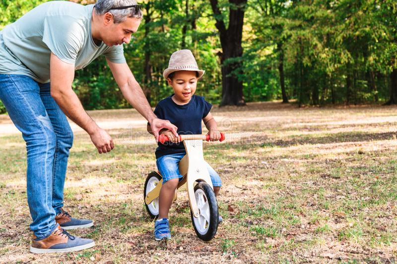 Father teaching his son to ride wooden bike in park stock images