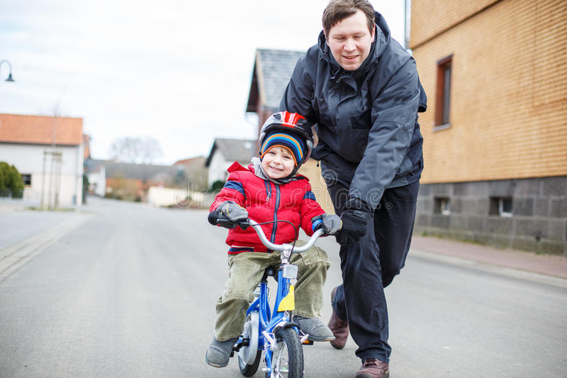 Father teaching his 3 years old son to ride a bike stock image