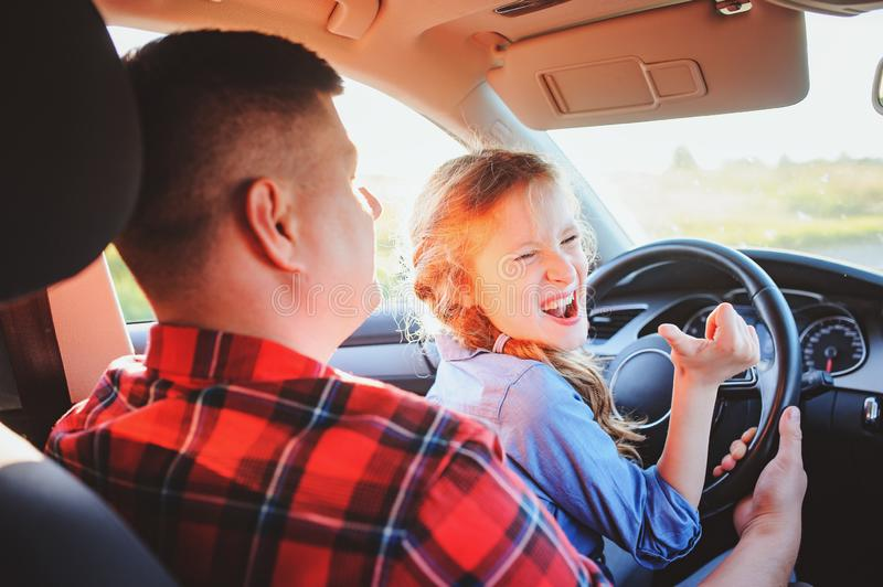 Father teaching kid daughter to drive a car, family traveling stock image