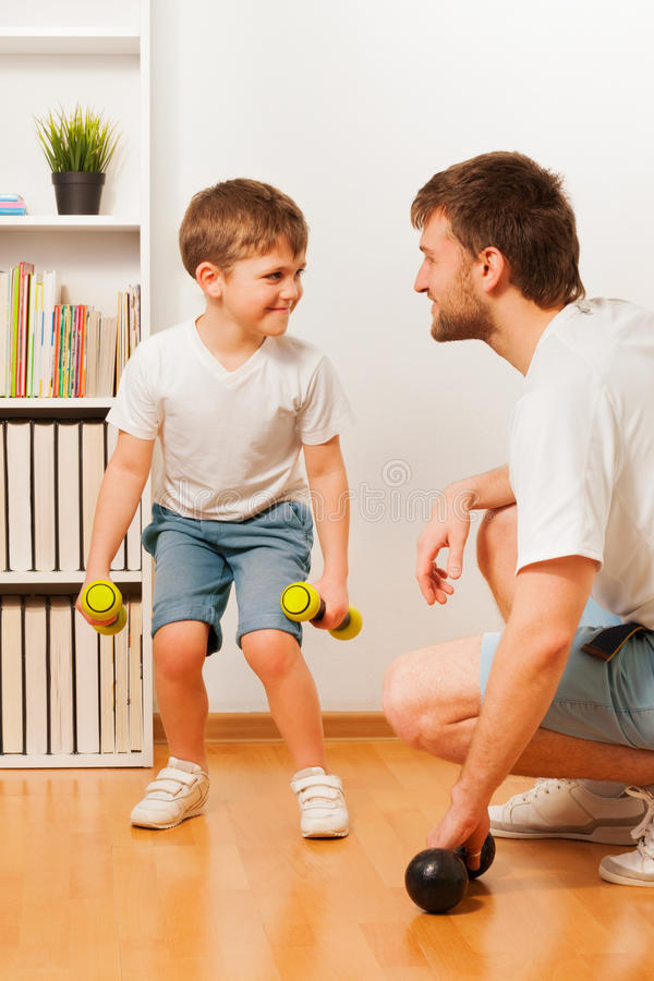 Father teaching son doing exercises with barbell stock photos