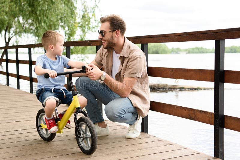 Father teaching son riding bike on bridge. At park royalty free stock photo
