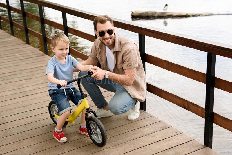 Father teaching son riding bike. At park stock photos