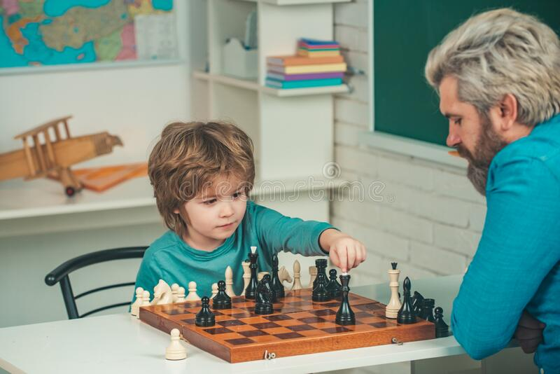 Father teaching son. Teacher and child. Parenthood. Back to school and Education concept. Boy think or plan about chess royalty free stock photography