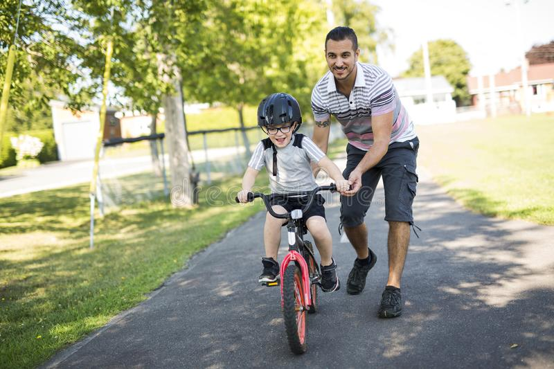Father Teaching Son To Ride Bicycle royalty free stock photo