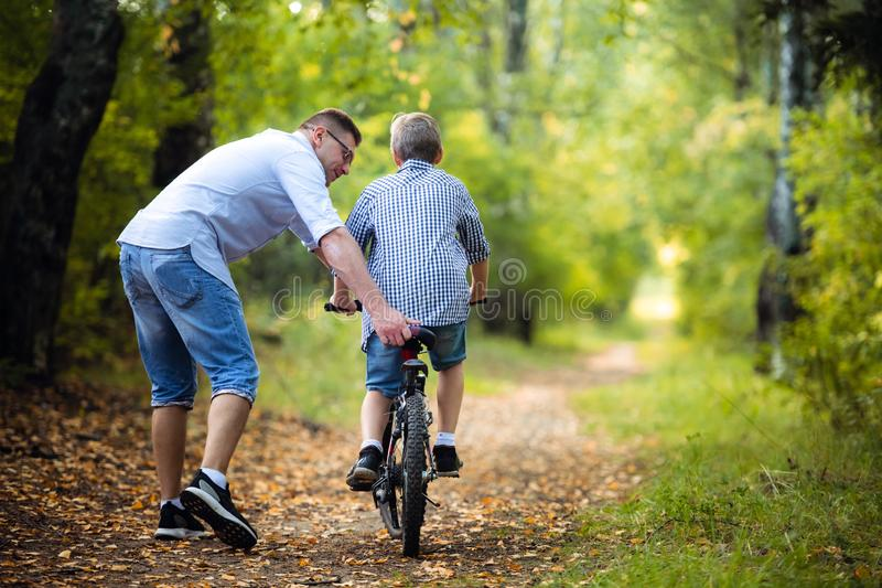 Father Teaching Son To Ride Bike In Countryside royalty free stock photography