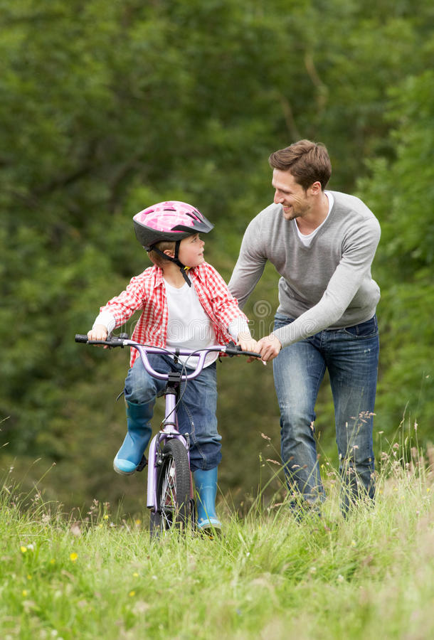 Father Teaching Son To Ride Bike In Countryside stock photos