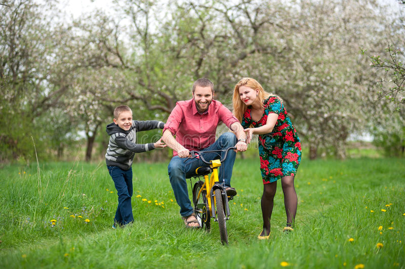 Father teaching son to ride a bike by his example stock images