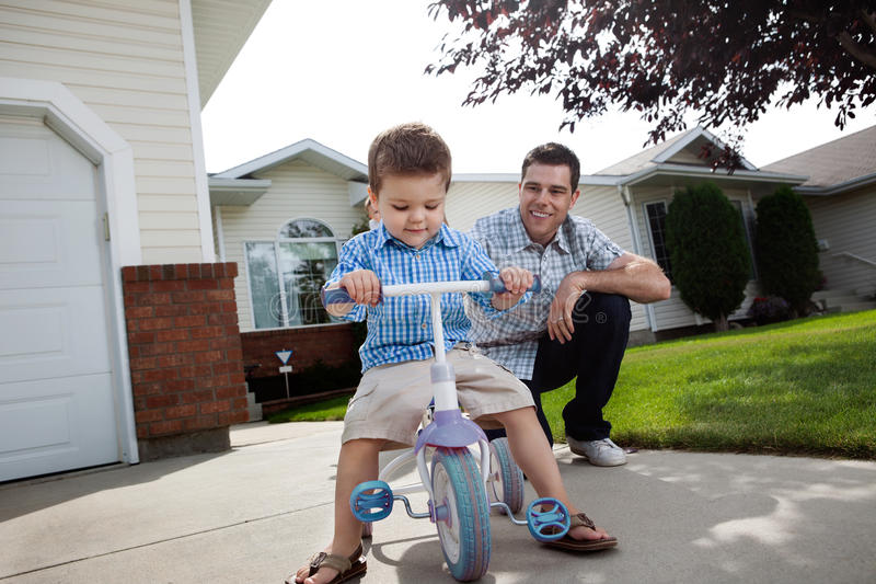 Father teaching Son To Ride a Tricycle royalty free stock photography