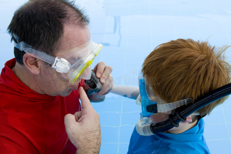 Father teaching son to snorkel royalty free stock photography