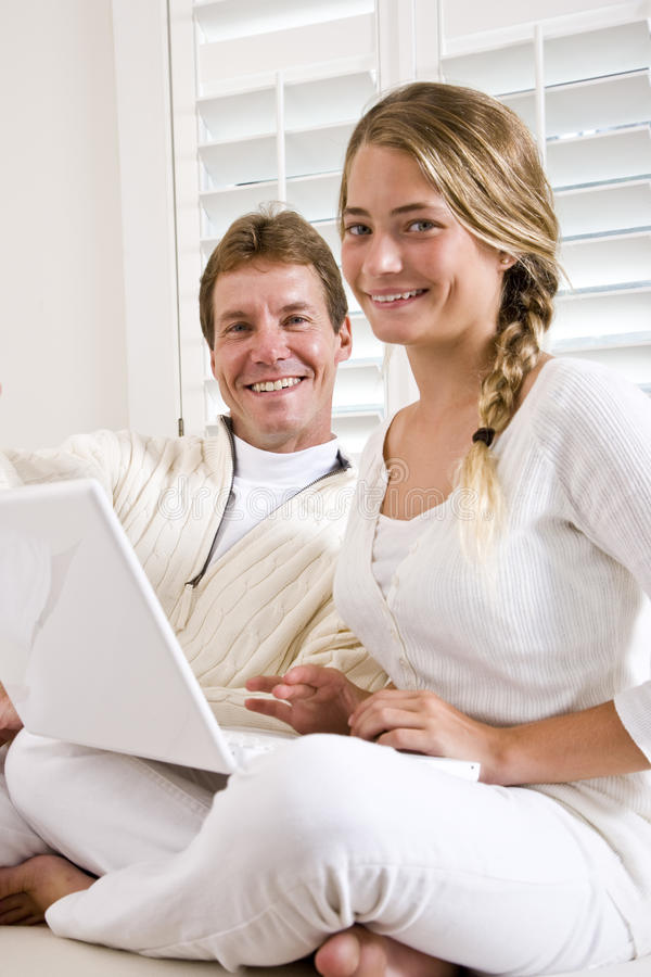 Father and teen daughter on white sofa with laptop stock image