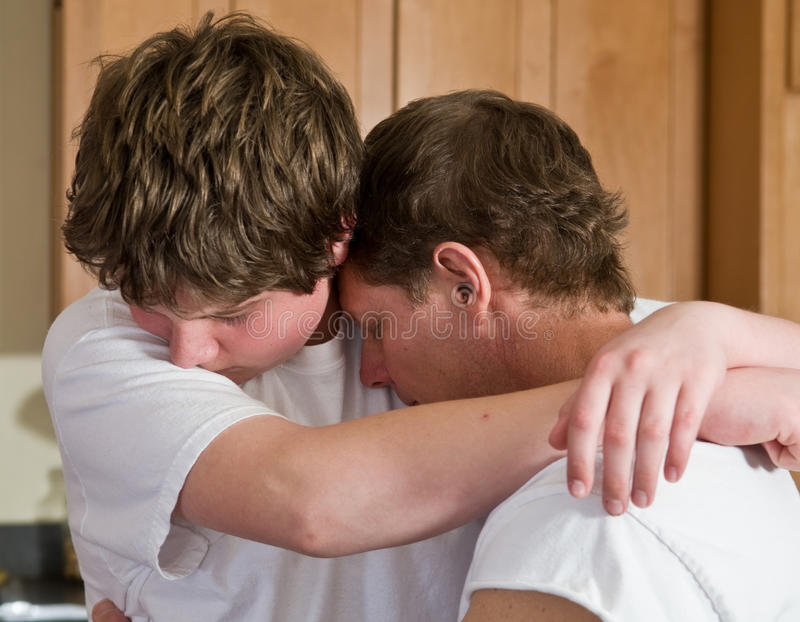 Father and teen son hugging stock image