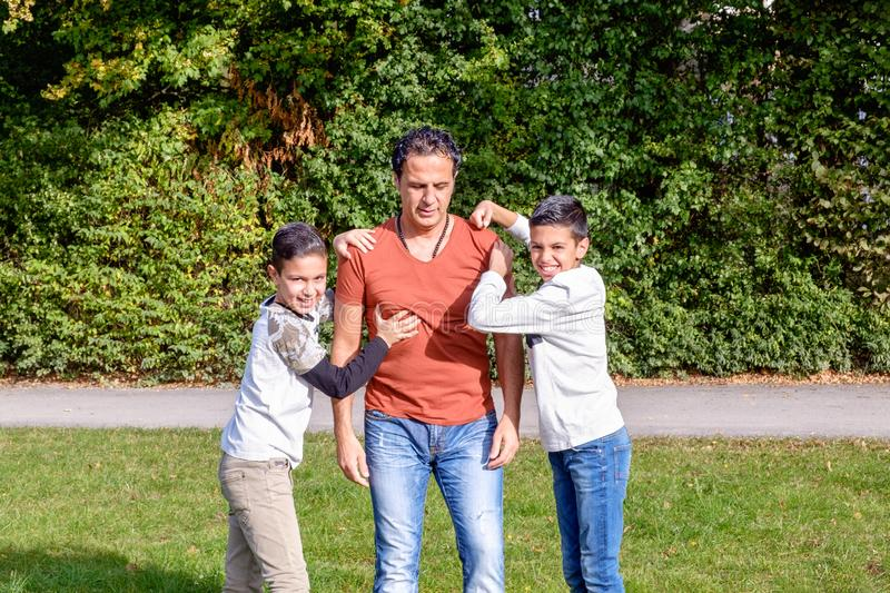 Father and teenage children in walking the park stock images