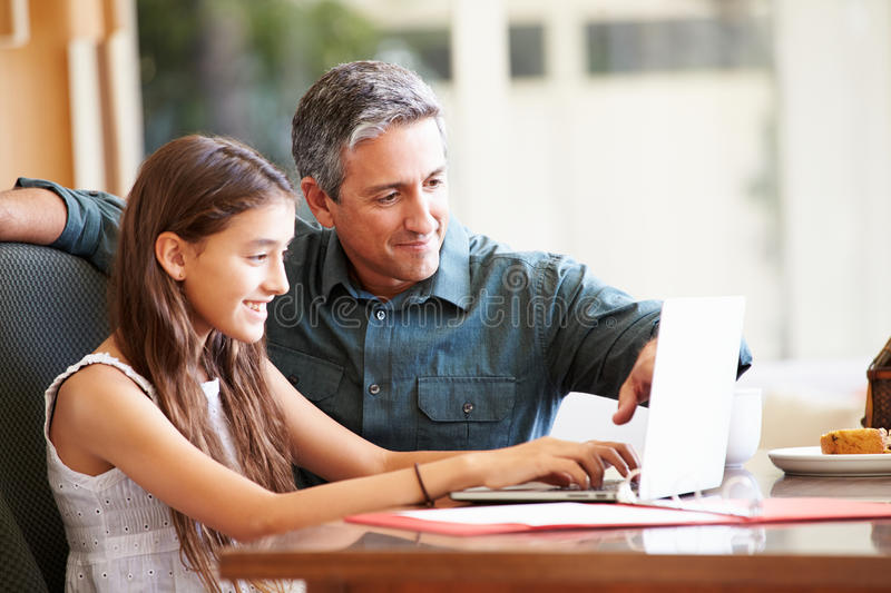 Father And Teenage Daughter Looking At Laptop Together. Browsing The Net Smiling royalty free stock images