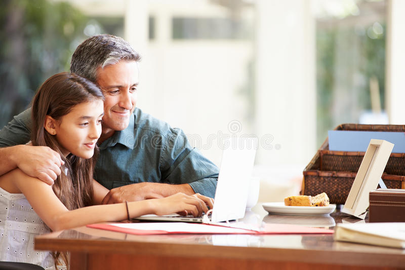 Father And Teenage Daughter Looking At Laptop Together. Happy Father And Teenage Daughter Looking At Laptop Together At Home royalty free stock photo
