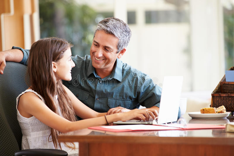 Father And Teenage Daughter Looking At Laptop Together. At Home Smiling stock images