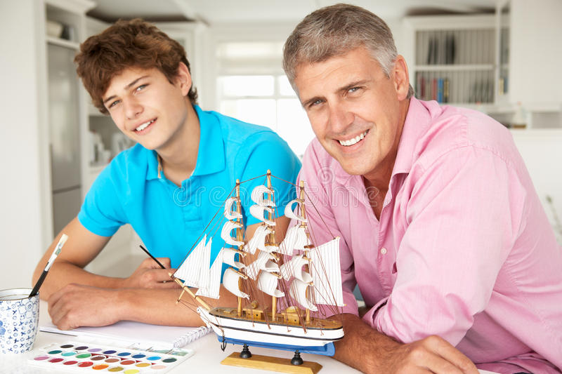 Father and teenage son model making. And painting both smiling at camera royalty free stock image