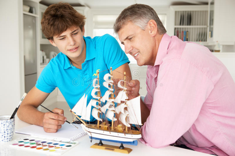 Father and teenage son model making and painting. A ship royalty free stock images