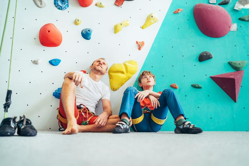 Father and teenage son sitting near the indoor climbing wall. They resting after the active climbing. Happy parenting concept stock image