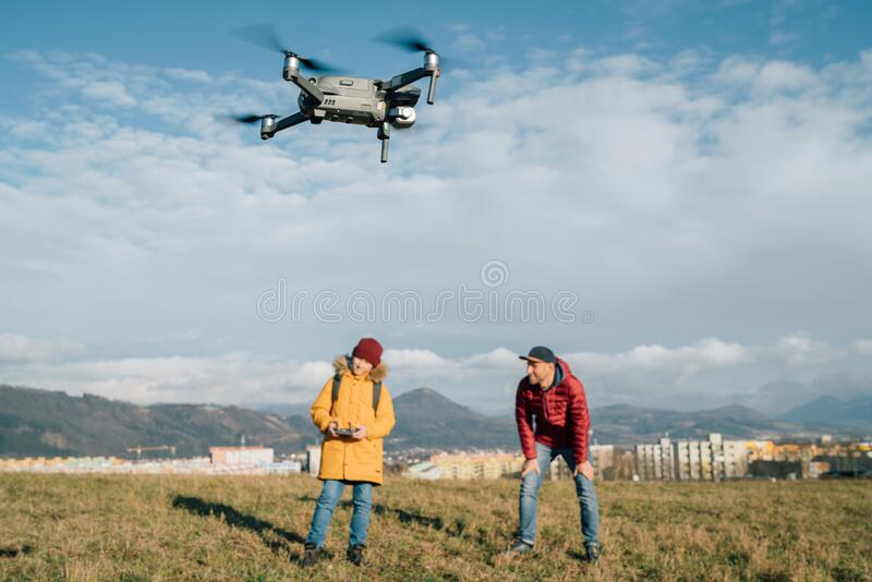Father and Teenager boy son dressed yellow jacket piloting a modern digital drone using remote controller. Modern technology. Devises concept image royalty free stock photography
