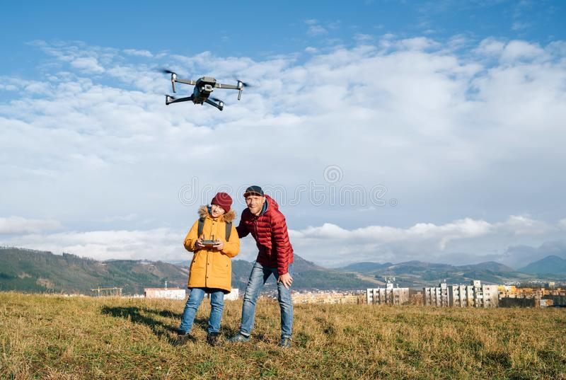 Father and Teenager boy son dressed yellow jacket piloting a modern digital drone using remote controller. Modern technology royalty free stock photography