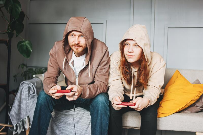Father and teenager daughter tween girl in hoodies playing computer games with joystick at home tipical caucasian family. Father and teenager daughter tween girl royalty free stock image