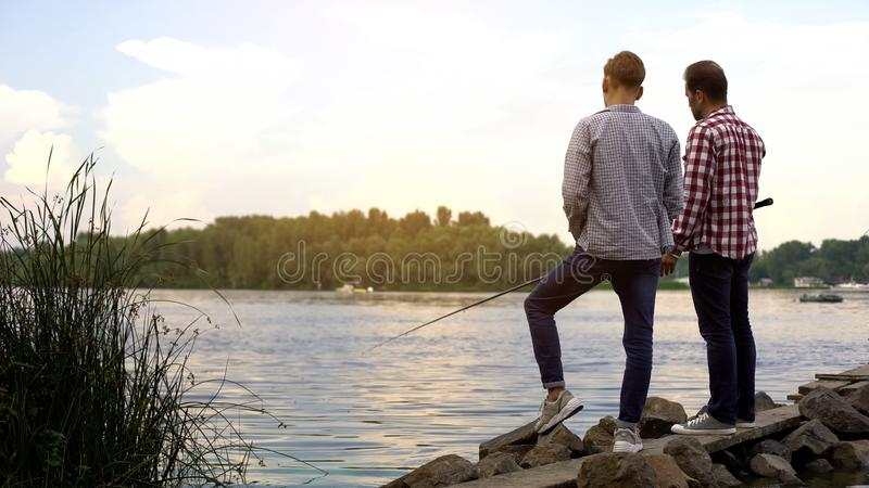 Father and teenager son fishing together, relaxing near lake, favorite hobby royalty free stock photography